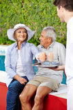 Two senior people relaxing at pool with cocktails Stock Photos