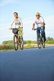 Two Senior People Riding Bikes In Summer Royalty Free Stock Images