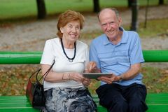 Two senior people sitting with a tablet PC Royalty Free Stock Photography