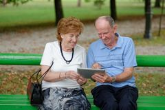 Two senior people sitting with a tablet PC Royalty Free Stock Image
