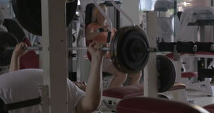 Two senior people training on fitness machines. Senior people having workout in the gym. Man lifting bar-bell and woman exercising on chest press machine stock video