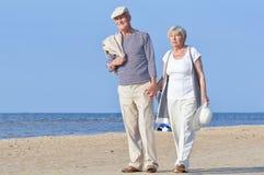 Two senior walking on a beach Stock Photo