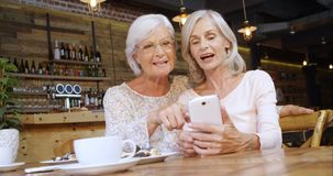 Senior woman discussing over the phone in cafe 4k stock footage