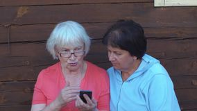 Two senior woman looking mobile phone and talking outdoor in countryside stock video footage