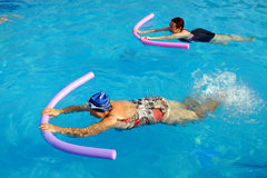 Two senior women doing swimming exercise in pool. Stock Image