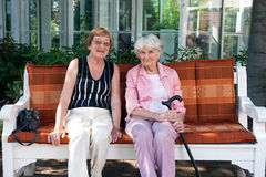 Two senior women enjoying a day outdoors. Two senior women enjoying a day outdoors sitting together on a wooden garden bench having a chat and smiling at the stock photo