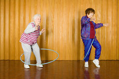 Two senior women exercising with hula hoops Royalty Free Stock Photo