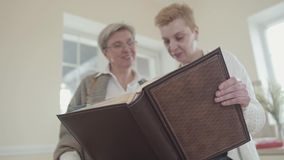 Two senior women holding big leather photo album and watching photos. Middle aged mature women communicating chatting. Spending time at home together stock video