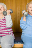 Two senior women lifting dumbbells Stock Photos