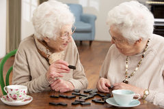 Two Senior Women Playing Dominoes royalty free stock image
