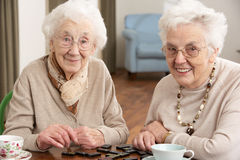 Two Senior Women Playing Dominoes