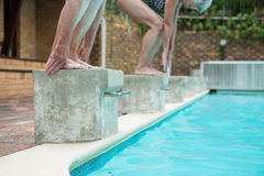 Two senior women preparing to dive in pool Royalty Free Stock Photography