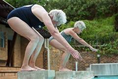 Two senior women preparing to dive in pool Royalty Free Stock Photos