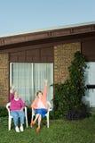 Two senior women sat in garden waving Stock Images