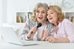 Two Senior women singing karaoke. With laptop at home royalty free stock photo