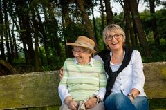 Two senior women sitting on a bench in a park, concept generations, family, care stock images