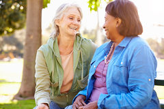 Two Senior Women Talking Outdoors Together stock photo