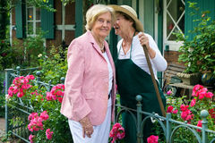 Two Senior Women Telling Secrets in Home Garden Royalty Free Stock Photography