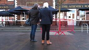 Two Senior Women Walking Past And Discussing Hospitality Industries JD Wetherspoons Pub Closures During COVID-19