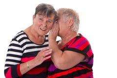 Two senior women whispering Stock Photos