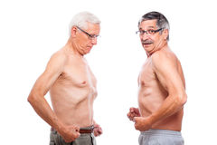 Two seniors comparing figure. Two naked seniors comparing figure, isolated on white background royalty free stock image