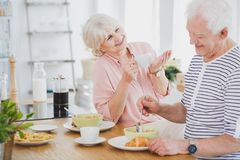 Two seniors talking during breakfast. Two lovely seniors talking and smiling while eating breakfast in a white, modern kitchen Stock Images