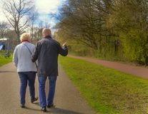 Two seniors walking in spring park stock photography