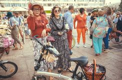 Two seniors women in vintage clothing meeting with youth during the city festival in Europe. Royalty Free Stock Photography