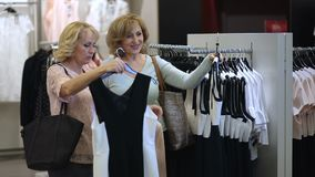 Two senoir women at boutique choosing dress. stock footage