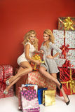 Two sensual girlfriends among Chritsmas gifts Stock Photos