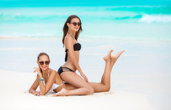 Two sensual women in bikini on a beach. Two beautiful young women,brunette in sun glasses,beautiful figure,dressed in a bikini black and white color ,wear Royalty Free Stock Image