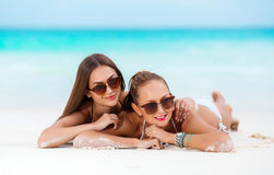Two sensual women in bikini on a beach. Two beautiful young women,brunette in sun glasses,beautiful figure,dressed in a bikini black and white color ,wear Royalty Free Stock Photos