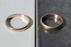 Two separate wedding rings on a black and white background. Concept - differences, opposites, and separation. Two separate wedding rings on a black and white stock images