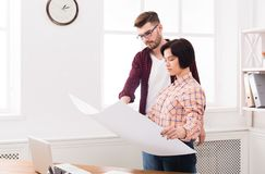 Two serious architects discussing building plan. Designers team working with new project in office, copy space Royalty Free Stock Image
