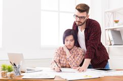 Two serious architects discussing building plan. Designers team working with new project in office, copy space Royalty Free Stock Photography