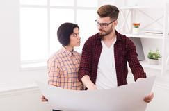 Two serious architects discussing building plan. Designers team working with new project in office, copy space Royalty Free Stock Images