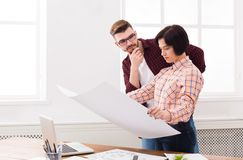 Two serious architects discussing building plan. Designers team working with new project in office, copy space Stock Image