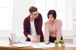 Two serious architects discussing building plan. Designers team working with new project in office, copy space Stock Images