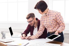 Two serious architects discussing building plan. With digital tablet. Designers team working with new project in office, copy space Royalty Free Stock Photography