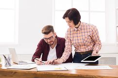 Two serious architects discussing building plan. With digital tablet. Designers team working with new project in office, copy space Stock Image