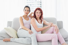 Two serious beautiful female friends sitting in living room Royalty Free Stock Photography