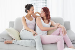 Two serious beautiful female friends sitting in living room Stock Photos