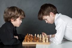 Two serious boy playing chess, studio Royalty Free Stock Photos