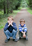 Two serious brother sitting on edge of  road. Two serious brother sitting on edge of road, park Royalty Free Stock Image