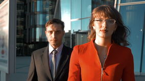 Two serious business people go. Slow motion. Two business colleagues walk near modern glass building, woman in red suit and spectacles, man in black. Teamwork stock video footage