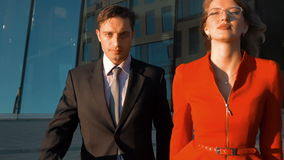 Two serious business people go. Slow motion. Two business colleagues walking against office building, experienced businessman and businesswoman professional stock video