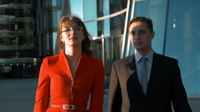 Two serious business people walking. Slow motion steadicam shot of young businessman and businesswoman seriously going to the deal. They walking in the business stock footage