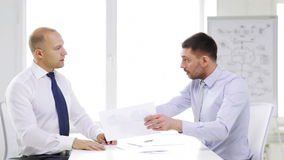 Two serious businessmen with charts in office. Business, partnership, finances and office concept - two serious businessmen holding papers and talking in office stock footage