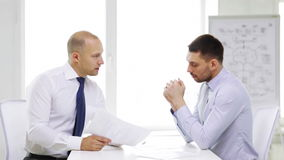 Two serious businessmen with charts in office. Business, partnership, finances and office concept - two serious businessmen holding papers and talking in office stock video footage