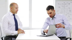 Two serious businessmen with laptop in office stock footage